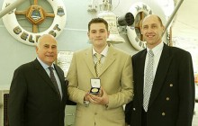 Medal of Excellence winner Colin Sanders is presented with his award aboard HMS Belfast